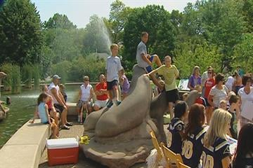 Children sit on top of a statue while waiting for the St. Louis Rams' new mascot debut at the St. Louis Zoo on Monday, July 26, 2010.