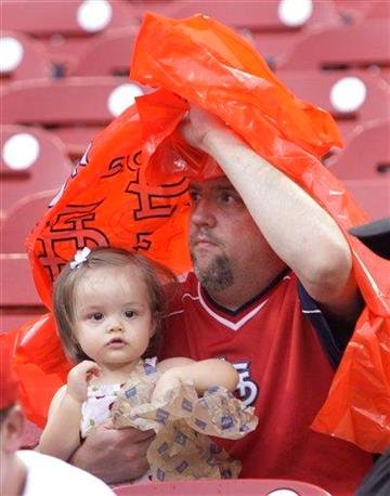 A young St. Louis Cardinals fan eats a snack as her father shields her from a light rain before a baseball game between the Pittsburgh Pirates and the Cardinals, Friday, July 30, 2010, in St. Louis. (AP Photo/Tom Gannam) By Tom Gannam