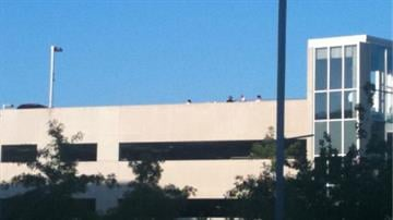 Unidentified persons stand atop the St. Johns Medical Mercy Center parking garage following a stabbing on August 3, 2010