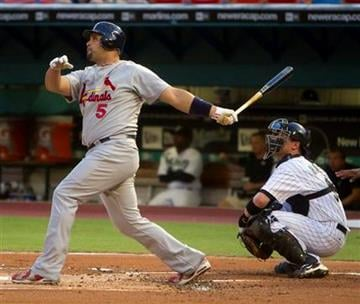 Florida Marlins catcher Brett Hayes, right, watches St. Louis Cardinals batter Albert Pujois (5) hit a first-inning three-run home run during baseball game action in Miami, Friday, Aug. 6, 2010. (AP Photo/J Pat Carter) By J Pat Carter