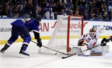 St. Louis Blues' David Backes, left, tries to sneak a puck past Calgary Flames goalie Miikka Kiprusoff, of Finland, during the second period of an NHL hockey game Friday, April 1, 2011, in St. Louis. (AP Photo/Jeff Roberson) By Jeff Roberson