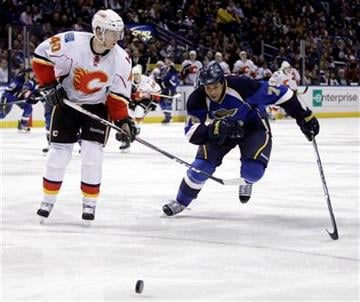 Calgary Flames' Alex Tanguay, left, and St. Louis Blues' Ryan Reaves chase after a loose puck during the second period of an NHL hockey game Friday, April 1, 2011, in St. Louis. (AP Photo/Jeff Roberson) By Jeff Roberson