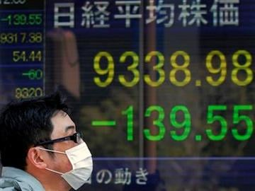 A man walks  in front of the electronic stock board of a securities firm in Tokyo, Japan, Tuesday,  March 29, 2011. The benchmark Nikkei 225 stock average lost 139.55 points, to end morning session at 9338.98. (AP Photo/Itsuo Inouye) By Itsuo Inouye