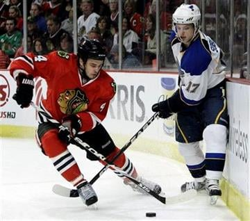 Chicago Blackhawks' Niklas  Hjalmarsson, left, and St. Louis Blues' Vladimir Sobotka battle for the puck during the first period of an NHL hockey game in Chicago, Wednesday, April 6, 2011. (AP Photo/Nam Y. Huh) By Nam Y. Huh