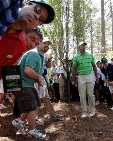 Spectators watch Tiger Woods' shot out of the rough off the third fairway during the first round of the Masters golf tournament Thursday, April 7, 2011, in Augusta, Ga. (AP Photo/David J. Phillip) By David J. Phillip