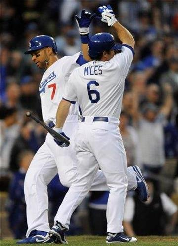 Los Angeles Dodgers' Aaron Miles (6) high-fives James Loney (7) as Loney scores on a Marcus Thames triple in the seventh inning of a baseball game against the San Francisco Giants, Sunday, April 3, 2011, in Los Angeles. (AP Photo/Gus Ruelas) By Gus Ruelas