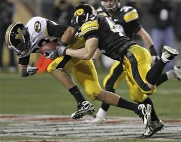 Missouri tight end Michael Egnew, left, is tackled by Iowa linebacker James Morris, right, during the third quarter of the Insight Bowl NCAA college football game Tuesday, Dec. 28, 2010, in Tempe, Ariz. (AP Photo/Paul Connors) By Paul Connors