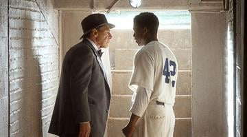 """(L-r) HARRISON FORD as Branch Rickey and CHADWICK BOSEMAN as Jackie Robinson in Warner Bros. Pictures' and Legendary Pictures' drama """"42,"""" a Warner Bros. Pictures release. By Courtesy of Warner Bros. Picture"""