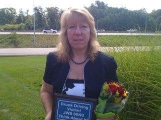 Jon Wade Smith's wife Roberta Illert holding replica sign . By Lakisha Jackson