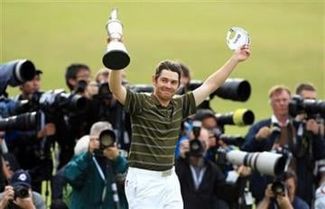 South Africa's Louis Oosthuizen holds his trophy aloft after winning the British Open Golf Championship on the Old Course at St. Andrews, Scotland, Sunday, July 18, 2010. (AP Photo/Tim Hales) By Tim Hales