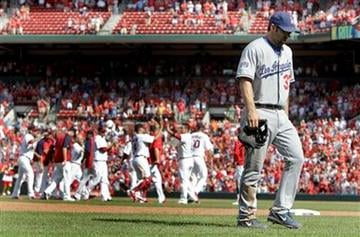 Los Angeles Dodgers' Blake DeWitt walks off the field as members of the St. Louis Cardinals celebrate their 5-4 victory in a baseball game Sunday, July 18, 2010, in St. Louis. (AP Photo/Jeff Roberson) By Jeff Roberson