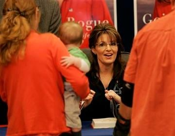 """Former Alaska Gov. Sarah Palin signs a copy her her autobiography, """"Going Rogue"""", at the North Post Exchange at Fort Bragg, N.C., Monday, Nov. 23, 2009. (AP Photo/Jim R. Bounds) By Jim R. Bounds"""