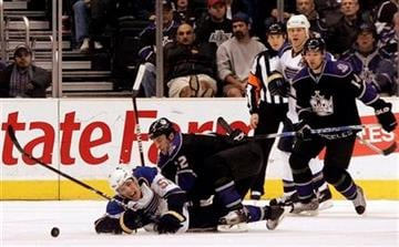 St. Louis Blues left wing David Perron (57) and Los Angeles Kings defenseman Randy Jones (12) go down as they pursue the puck in the second period of an NHL hockey game in Los Angeles on Saturday, Dec. 5, 2009.  (AP Photo/Jason Redmond) By Jason Redmond