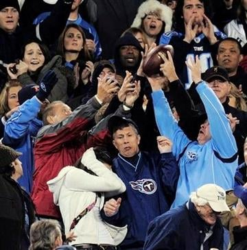 Fans try to catch a football thrown into the stands by a player in the third quarter of an NFL football game between the St. Louis Rams and the Tennessee Titans on Sunday, Dec. 13, 2009, in Nashville, Tenn. (AP Photo/John Russell) By John Russell