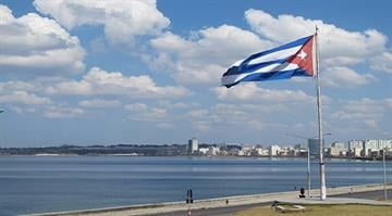 The Cuban flag flies along a Havana beach. By Stephanie Baumer