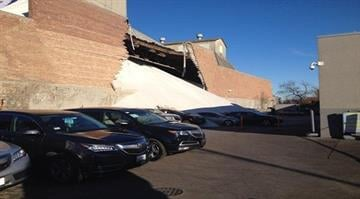 An overburdened wall at a salt warehouse in Chicago, Illinois, collapses Tuesday, Dec. 30, 2014, spilling a mountain of white crystals on cars parked at a neighboring Acura dealership By Stephanie Baumer