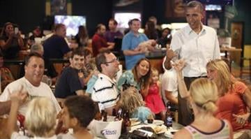 President Barack Obama points at Andre Wupperman, far left, during a stop at Gator's Dockside, Saturday, Sept. 8, 2012, in Orlando, Fla.
