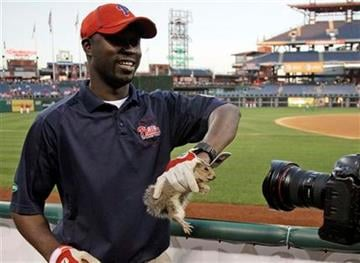 Philadelphia Phillies grounds keeper Soule Sidibe holds a squirrel he caught before baseball's Game 5 of the National League division series with the St. Louis Cardinals Friday, Oct. 7, 2011 in Philadelphia. (AP Photo/Matt Slocum) By Matt Slocum