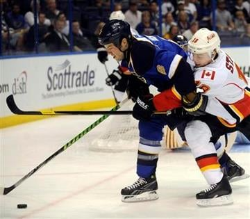 St. Louis Blues' Kent Huskins (6) and Calgary Flames' Matt Stajan reach for the puck in the first period of an NHL hockey game Monday, Oct. 10, 2011, in St. Louis. (AP Photo/Bill Boyce) By Bill Boyce