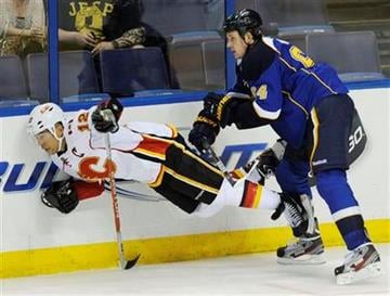 St. Louis Blues' Nikita Nikitin (64), of Russia, checks Calgary Flames' Jarome Iginla (12) in the third period of an NHL hockey game Monday, Oct. 10, 2011, in St. Louis. (AP Photo/Bill Boyce) By Bill Boyce