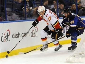 Calgary Flames' Rene Bourque (17) and St. Louis Blues' Alex Pietrangelo (27) battle for the puck in the first period of an NHL hockey game Monday, Oct. 10, 2011, in St. Louis. (AP Photo/Bill Boyce) By Bill Boyce