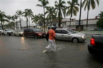 A pedestrian walks on a flooded street in Puerto Vallarta, Mexico, Monday Oct. 10, 2011. Hurricane Jova strengthened to a major, Category 3 hurricane Monday as it marched toward Mexico's Pacific coast. (AP Photo/Marco Ugarte) By Marco Ugarte