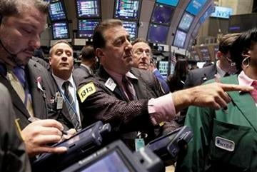 Stephen Holden, center, works on the floor of the New York Stock Exchange with fellow traders, Wednesday, Oct. 12, 2011. (AP Photo/Richard Drew) By Richard Drew