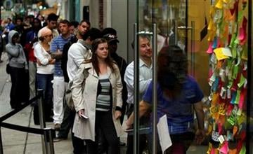 Customers wait in line to purchase the new iPhone 4S in view of a makeshift memorial to deceased Apple co-founder Steve Jobs outside of an Apple store Friday, Oct. 14, 2011, in Philadelphia. (AP Photo/Matt Rourke) By Matt Rourke
