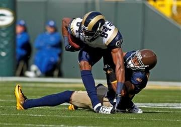 Green Bay Packers cornerback Tramon Williams, bottom right, tackles St. Louis Rams wide receiver Danario Alexander (84) during the first half of an NFL football game Sunday, Oct. 16, 2011, in Green Bay, Wis. (AP Photo/Jeffrey Phelps) By Jeffrey Phelps