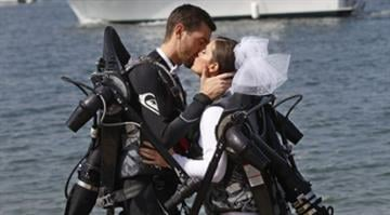 Grant Engler and his new wife, Amanda Engler, wearing jetpack suits, kiss after being pronounced married at their wedding ceremony, Aug. 23, 2012 in Newport Beach, Calif. (AP Photo/Lenny Ignelzi) By Brendan Marks