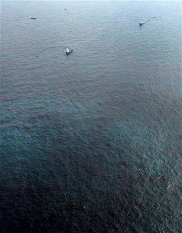 Support vessels place a booms in oily water at the site of the Deepwater Horizon oil spill in the Gulf of Mexico off the coast of Louisiana Wednesday, May 12, 2010. (AP Photo/Charlie Riedel) By Charlie Riedel