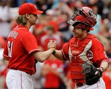 Cincinnati Reds starting pitcher Bronson Arroyo (61) is congratulated by catcher Ryan Hanigan after throwing a complete baseball game to defeat the St. Louis Cardinals 7-2 on Sunday, May 16, 2010, in Cincinnati. (AP Photo/Al Behrman) By Al Behrman