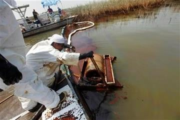 A contractor operates an oil skimmer as EPA Administrator Lisa Jackson tours marshes impacted from the Deepwater Horizon oil spill in Pass a Loutre, La. on Monday, May 24, 2010.  (AP Photo/Gerald Herbert) By Gerald Herbert