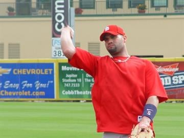 Albert Pujols tosses a ball back to back to the infield during infielder's practice Wednesday morning. By Lakisha Jackson