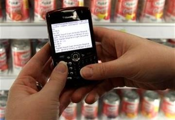 In this photo made Dec. 8, 2009, Kelly Norby searches coupontom.com on her Blackberry to find coupons for Yoplait brand yogurt at a Target store in Wheeling, Ill. (AP Photo/M. Spencer Green) By M. Spencer Green