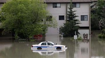 A police car sits stuck in a parking lot of an apartment building after heavy rains have caused flooding, closed roads, and forced evacuation in Calgary, Alberta, Canada Friday, June 21, 2013. (AP Photo/The Canadian Press, Jeff McIntosh) By Dan Mueller
