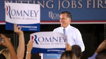 Republican Presidential candidate Mitt Romney smiles to supporters as he takes to the stage during a campaign stop at Production Products in St. Louis on June 7, 2012. By Brendan Marks