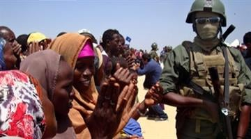 Somali women, residents of Mogadishu, cheer as an armed security officer keeps watch March 6, 2012, after a Turkish Airlines aircraft arrived on its maiden commercial flight into the war-torn Somalia capital. (AFP/Getty Images) By Brendan Marks