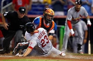 MIAMI, FL - JUNE 27:  John Buck #14 of the Miami Marlins tags out David Freese #23 of the St. Louis Cardinals during a game at Marlins Park on June 27, 2012 in Miami, Florida.  (Photo by Sarah Glenn/Getty Images) By Sarah Glenn