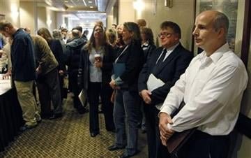 FILE - In this Dec. 2, 2011 file photo, people wait in line to enter a job fair, in Portland, Ore. (AP Photo/Rick Bowmer, File) By Rick Bowmer