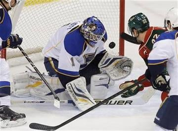 St. Louis Blues goalie Brian Elliott (1) stops a shot as Minnesota Wild's Cal Clutterbuck (22) looks for a rebound in the first period of an NHL hockey game on Thursday, April 11, 2013 in St. Paul. (AP Photo/Jim Mone) By Jim Mone
