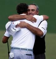 Angel Cabrera, right, of Argentina, hugs Adam Scott, of Australia, after Scott made a birdie putt on the second playoff hole to win the Masters golf tournament Sunday, April 14, 2013, in Augusta, Ga. (AP Photo/David Goldman) By David Goldman
