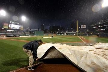A PNC Park grounds crew member helps covers the field in the rain during the second inning of a baseball game between the Pittsburgh Pirates and St. Louis Cardinals in Pittsburgh, Tuesday, April 16, 2013. (AP Photo/Gene J. Puskar) By Gene J. Puskar