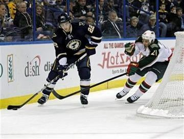 Minnesota Wild's Kyle Brodziak (21) reaches to knock the puck away from St. Louis Blues' Kevin Shattenkirk (22) during the first period of an NHL hockey game, Saturday, Feb. 18, 2012 in St. Louis.(AP Photo/Tom Gannam) By Tom Gannam