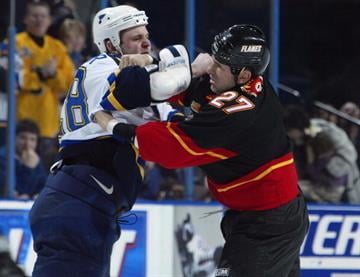 ST. LOUIS - FEBRUARY 17:  Matt Walker #28 of the St. Louis Blues and Craig Berube #27 of the Calgary Flames trade blows on February 17, 2003 at the Savvis Center in St. Louis, Missouri. The Blues won 5-3.(Photo by Elsa/Getty Images/NHLI) By Elsa
