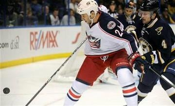 St. Louis Blues' Kris Russell (4) vies for a loose puck with Columbus Blue Jackets' Derek MacKenzie (24) in the first period of an NHL hockey game Sunday, Dec. 18, 2011, in St. Louis. (AP Photo/Bill Boyce) By Bill Boyce