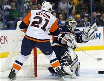 New York Islanders' Kyle Okposo (21) tries to knock the loose puck away from St. Louis Blues goalie Chris Mason in the first period of an NHL hockey game, Saturday, Nov. 21, 2009, in St. Louis. (AP Photo/Tom Gannam) By Tom Gannam