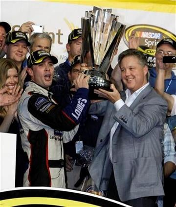 Jimmie Johnson, left, raises the trophy with NASCAR chairman Brian France, right, after winning the NASCAR Sprint Cup Series season championship at Homestead-Miami Speedway in Homestead, Fla., Sunday, Nov. 22, 2009. (AP Photo/Chuck Burton) By Chuck Burton