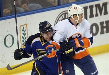 New York Islanders Matt Carkner (R) uses his stick to keep St. Louis Blues Magnus Paajarvi of Sweden from getting to the puck in the first period at the Scottrade Center in St. Louis on December 5, 2013. UPI/Bill Greenblatt By BILL GREENBLATT
