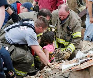 A child is pulled from beneath a collapsed wall at the Plaza Towers Elementary School in following a tornado in Moore, Okla., Monday, May 20, 2013. (AP Photo Sue Ogrocki) By Sue Ogrocki